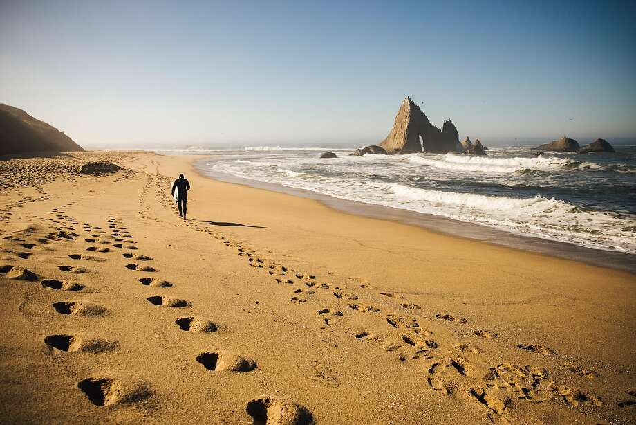 Jameson Kenway walks back to his car for work after an hour of surfing at Martins Beach in Half Moon Bay, Calif. Thursday, October 26, 2017. smaller photo; Jameson Kenway grabs his surf board for a morning surf on Martins Beach in Half Moon Bay, Calif. Thursday, October 26, 2017. Photo: Mason Trinca, Special To The Chronicle