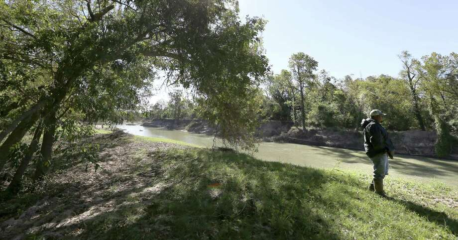 Ranch worker John Rodriguez stands next to the Guadalupe River on Errol John Dietze's property near Cuero, where floodwaters and wind from Hurricane Harvey toppled numerous pecan trees and ruined the entire crop. Photo: William Luther /San Antonio Express-News / © 2017 San Antonio Express-News