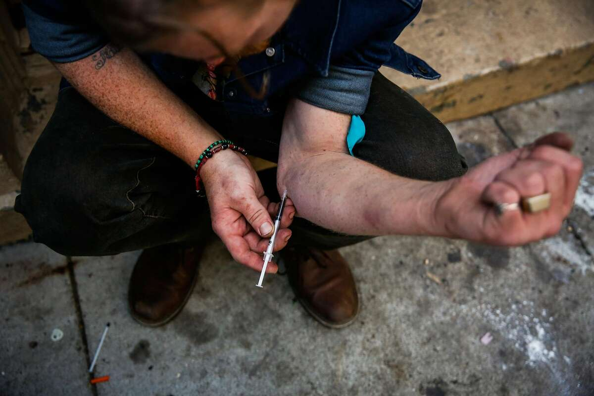 Spencer injects himself with heroin on Redwood Street in San Francisco, Calif., on Thursday, Oct. 26, 2017.