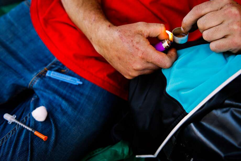 A user named Shawn heats up heroin before shooting up on Larkin Street in San Francisco on a sunny weekday. Photo: Gabrielle Lurie, The Chronicle
