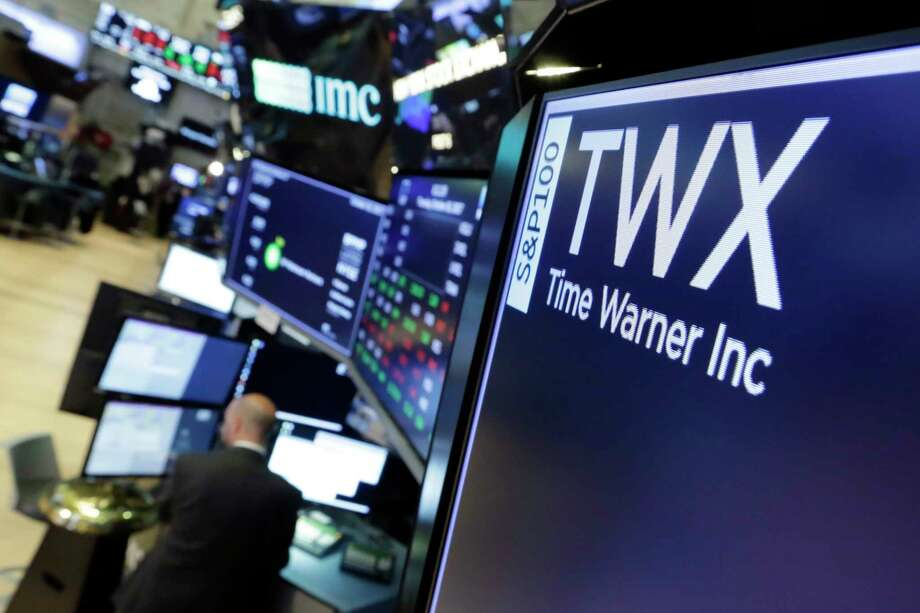 The symbol for Time Warner appears on a board above the floor of the New York Stock Exchange, Thursday, Oct. 26, 2017. Time Warner Inc. reported financial results for its third quarter that ended Sept. 30, 2017. (AP Photo/Richard Drew) Photo: Richard Drew, STF / AP