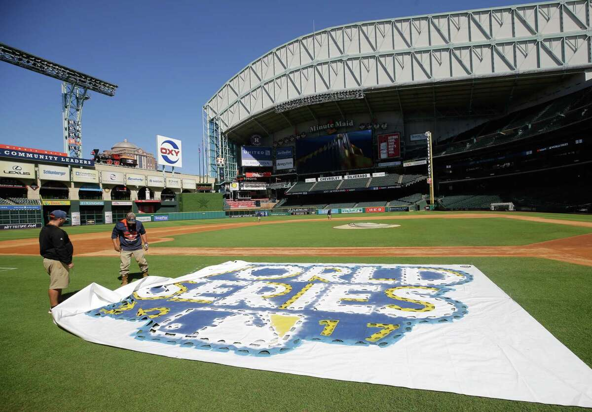 Jake Cooley, left, and James Vaughn, right, layout a stencil for the MLB World Series logo as the Astros groundcrews begin to paint at Minute Maid Park Wednesday, Oct. 25, 2017 in Houston.
