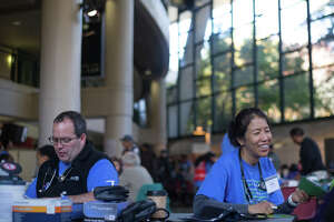 Volunteer nurses help patients with base-level checkups at the Seattle/King County Clinic at KeyArena on Thursday, Oct. 26, 2017.