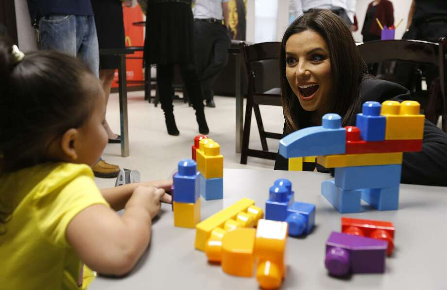 Actress and philanthropist Eva Longoria visits Thursday with Azalea Flores, 3, while touring The Grove apartment complex's new resident enrichment center on San Antonio's North Side. Longoria is an investor and ambassador for the Turner Multifamily Impact Fund, a real estate investment that aims to preserve affordable housing for working families. Photo: Edward A. Ornelas /San Antonio Express-News / © 2017 San Antonio Express-News