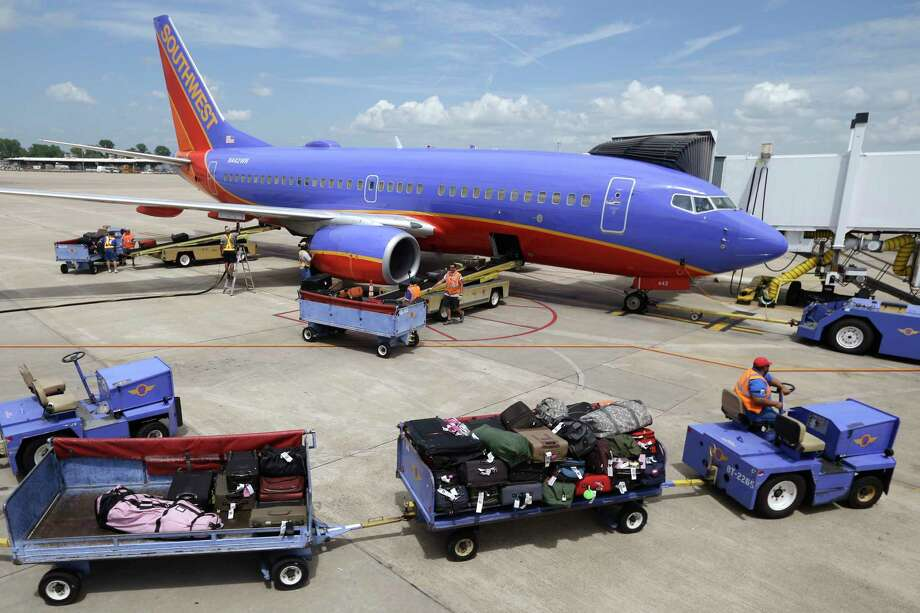 FILE - In this June 19, 2014 file photo, baggage carts are towed to a Southwest Airlines jet at Bill and Hillary Clinton National Airport in Little Rock, Ark., as the Boeing 737 is serviced. Southwest Airlines Co. reports earnings Thursday, Oct. 26, 2017. (AP Photo/Danny Johnston, File) Photo: Danny Johnston / Copyright 2017 The Associated Press. All rights reserved.