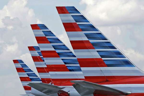 FILE - This July 17, 2015, file photo shows the tails of four American Airlines passenger planes parked at Miami International Airport, in Miami. On Thursday, Oct. 26, 2017, American Airlines Group, Inc. reports financial results. (AP Photo/Alan Diaz, File) ORG XMIT: NYBZ408