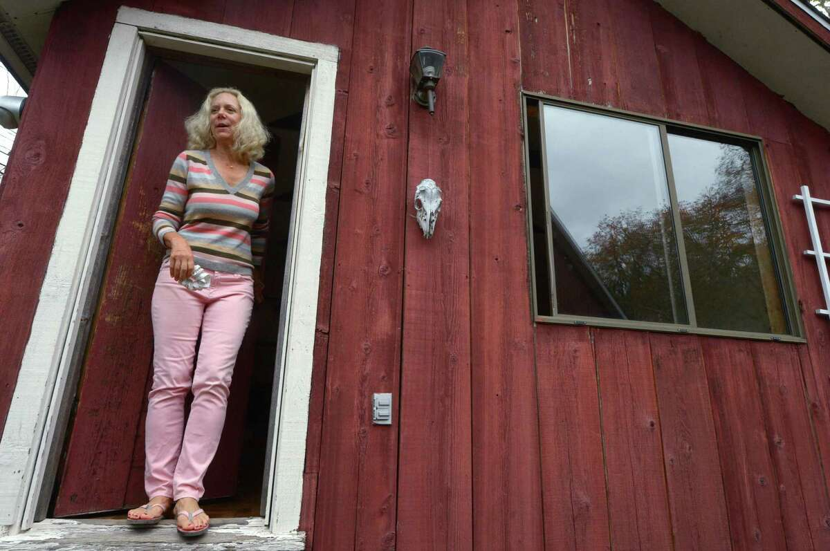 Homeowner Donna Conway exits one of the cabins at her home at 808 Ridgefield Road on Tuesday.