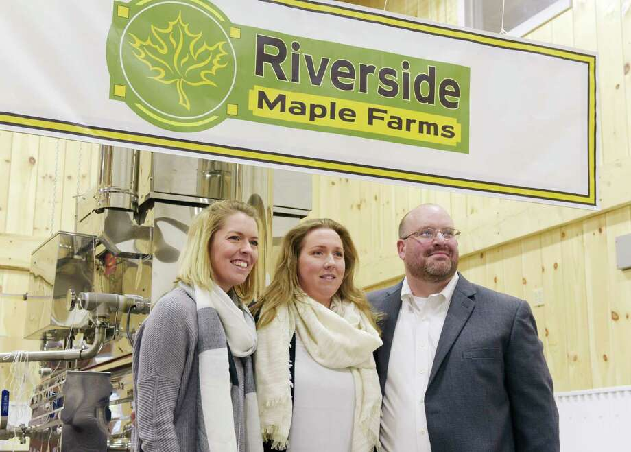 Emily Gierke, left, poses with her sister, Erica Welch and Erica's husband, Chris Welch during the grand opening of Welch's new business, Riverside Maple Farms on Thursday, Oct. 26, 2017, in Glenville, N.Y.  Gierke is the manager of the retail store at the maple farm.  The farm will offer tours of the of the working facility, which produces maple syrup, candies, maple spread, maple cotton candy and other products.  The retail store is open to the public year round.   (Paul Buckowski / Times Union) Photo: PAUL BUCKOWSKI / 20041949A