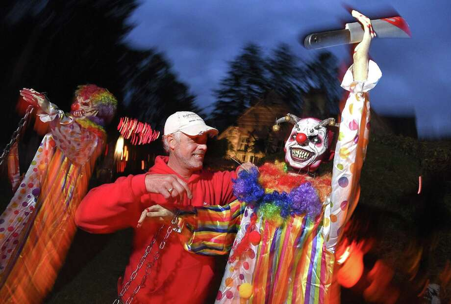 Vinny Pelazza Jr. adjusts one of several clowns he has decorated for his Halloween display in front of his home on Interlaken Road in Stamford on Thursday. The elaborate display, a collection of items he has collected over the years, includes several ghouls, skeletons, a graveyard and zombies of the night. Photo: Matthew Brown / Hearst Connecticut Media / Stamford Advocate