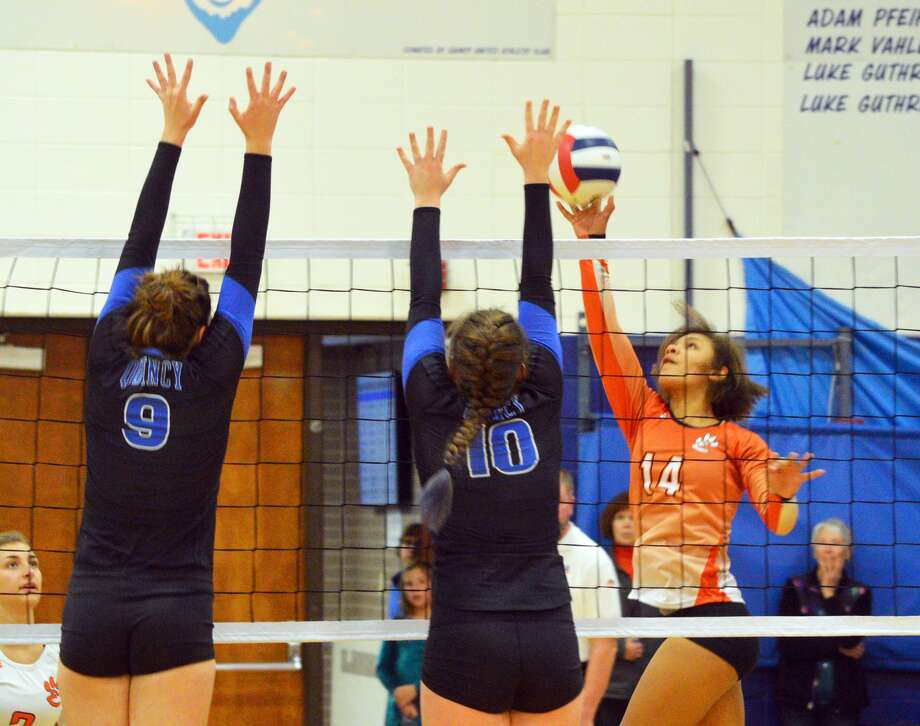 Edwardsville sophomore Maria Smith, right, tries to tip a ball over two Quincy blockers during the championship match of the Class 4A Quincy Regional on Thursday.