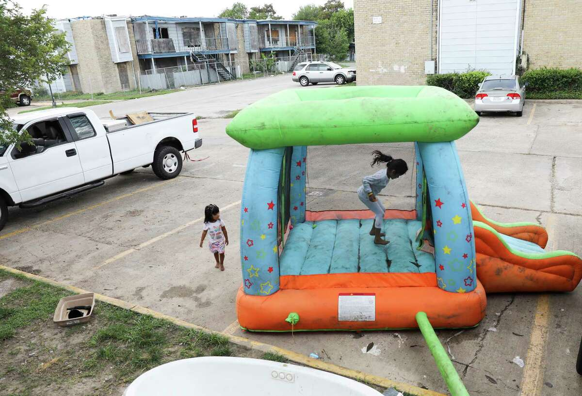 Monica Cruz jumps in an inflatable bouncy house in the parking lot at Rockport Apartments. Some tenants are making their own repairs to their apartments flooded by Hurricane Harvey.