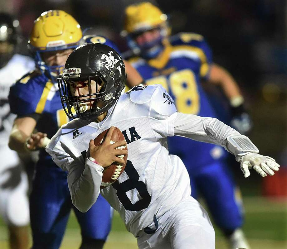 Ansonia senior quarterback Justin Lopez breaks past Seymour defense, Thursday, Oct. 26, 2017, in a Naugatuck Valley League game at Seymour High School.  Ansonia defeated Seymour, 61-6. Photo: Catherine Avalone / Hearst Connecticut Media / New Haven Register