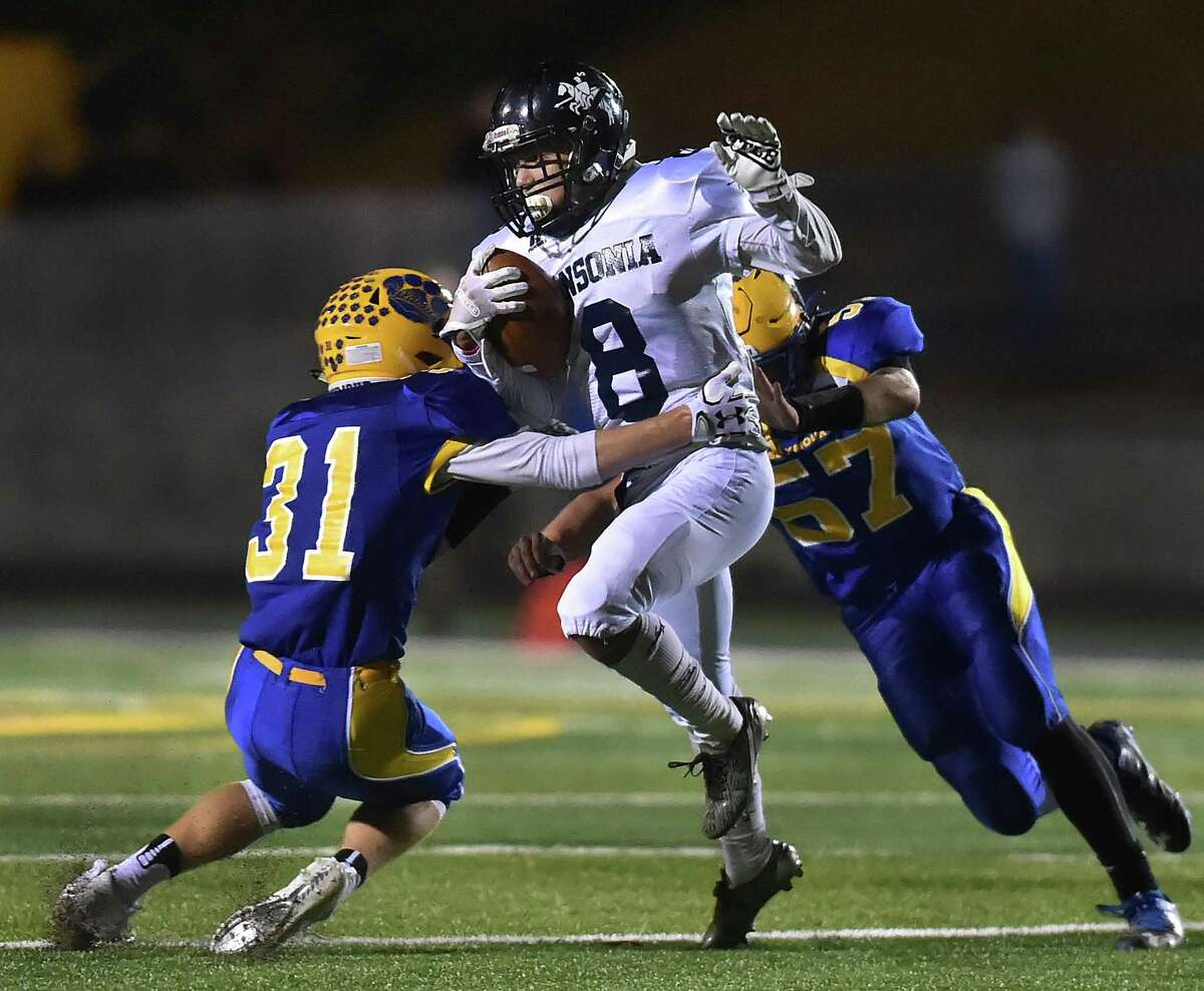 Ansonia senior quarterback Justin Lopez breaks past Seymour junior defensive back Tyler Ganim (#31) and senior defensive lineman Kyle Baxter (#57) Thursday, Oct. 26, 2017, at Seymour High School. Ansonia defeated Seymour, 61-6.