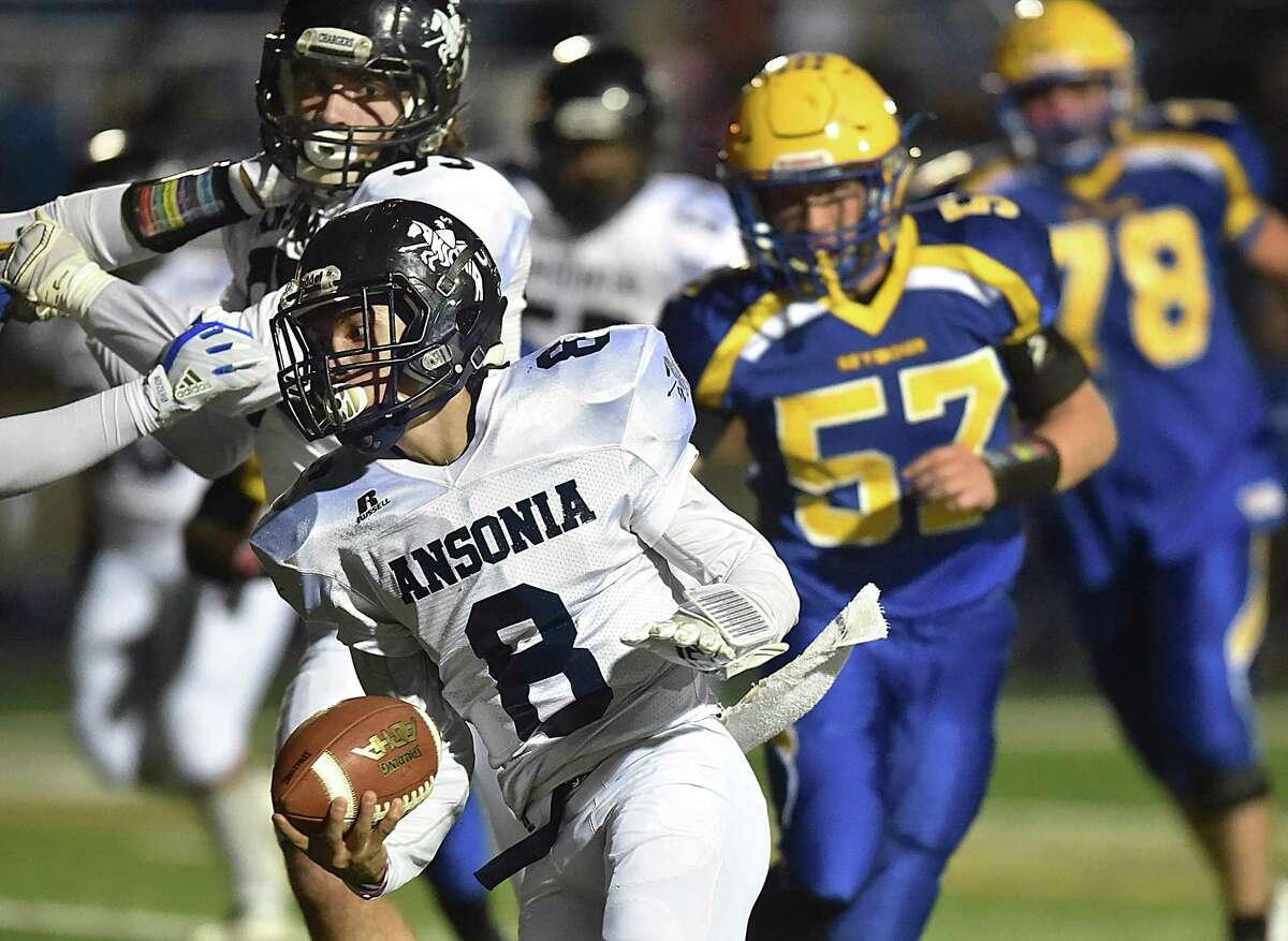 Ansonia senior quarterback Justin Lopez breaks past Seymour senior defensive linemen Kyle Baxter (57) and Anthony Mollo (78), Thursday, Oct. 26, 2017, at Seymour High School. Ansonia defeated Seymour, 61-6.