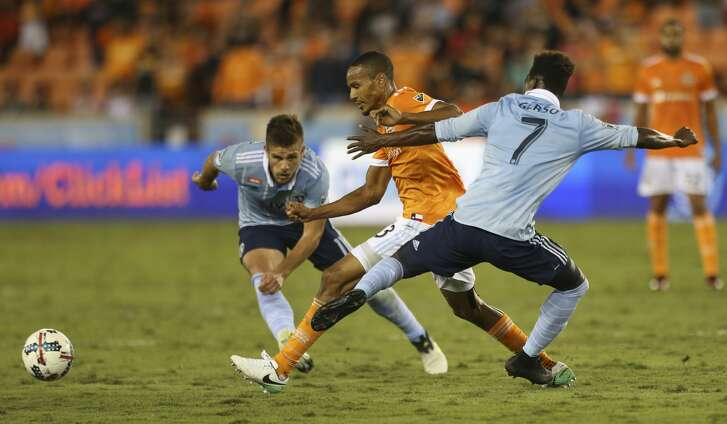 Houston Dynamo midfielder Ricardo Clark (13) battles with Sporting Kansas City players Diego Rubio (11) and Gerso Fermandes (7) for control of the ball during the first half of the first-round playoff MLS match at BBVA Compass Stadium Thursday, Oct. 26, 2017, in Houston. ( Yi-Chin Lee / Houston Chronicle )