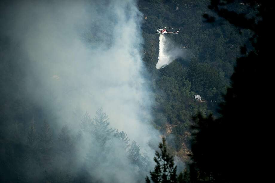 A helicopter drops water on the Bear fire in Boulder Creek, Calif., on Tuesday, Oct. 17, 2017. Photo: Noah Berger, Special To The Chronicle