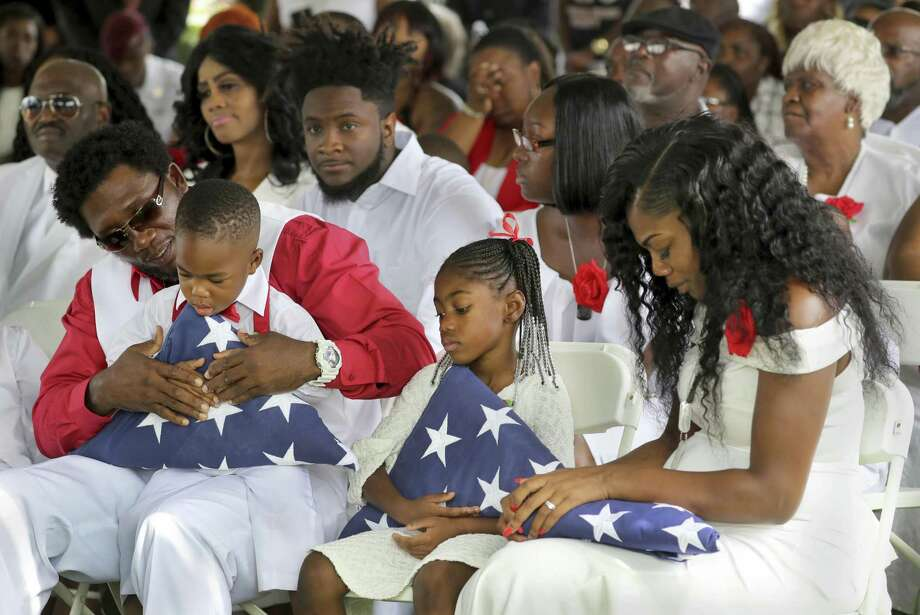 From left, Richard Johnson Sr. holds La David Johnson Jr,. Ah'Leesya Johnson, and Myeshia Johnson, the wife of Army Sgt. La David Johnson, attend Sgt. Johnson's burial at the Hollywood Memorial Gardens in Hollywood, Fla., on Oct. 21. He was killed with three other colleagues in an ambush by extremists in Niger on Oct. 4. Photo: Mike Stocker /Associated Press / Sun Sentinel 2016