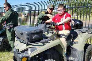 A U.S. Border Patrol agent explains to Daniel Garcia, a Harmony School of Innovation student, how an all-terrain vehicle works during the Careers on Wheels event held Thursday.
