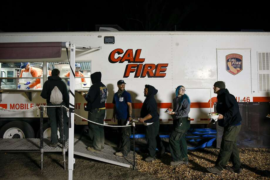 Crew members with Diamond Fire from Oregon, line up to get food after working a 16 hour day working on the fire lines, at the CalFire camp and operations center at the Sonoma County Fairgrounds in Santa Rosa, Calif, on Thursday October 12, 2017. Photo: Michael Short, Special To The Chronicle
