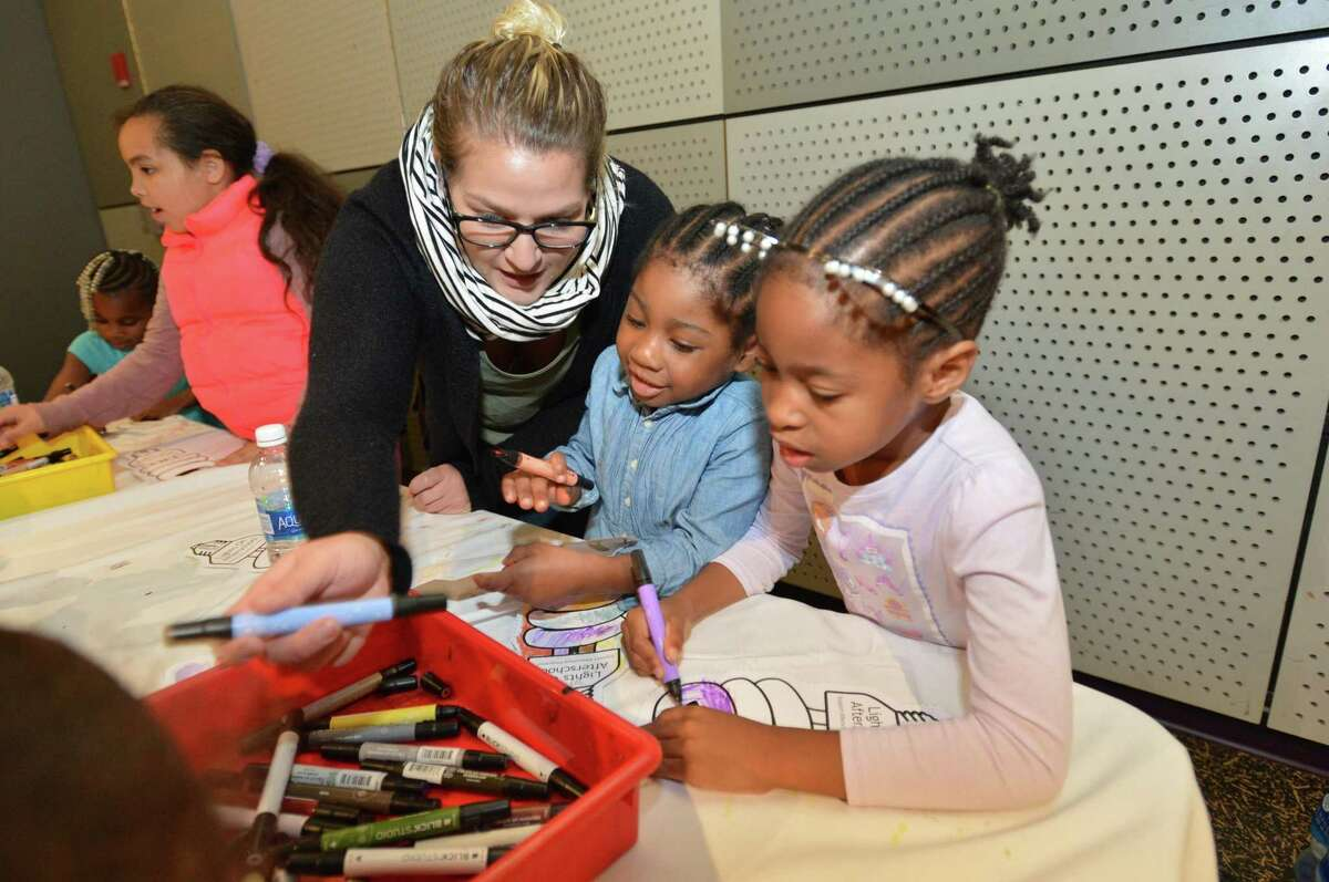 Art teacher Danielle Daniels colors with Chelsea Toussant and Christina Antoine during the Norwalk Housing Authority Learning Centers Lights On Afterschool celebration at Stepping Stones Museum for Children on Thursday, Oct. 26 in Norwalk.