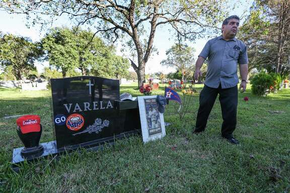 Christopher Varela and his siblings have been decorating his dad's (Joe G. Varela Sr.,) grave with Astros gear in Forest Park Lawndale Cemetery Thursday, Oct. 26, 2017, in Houston.