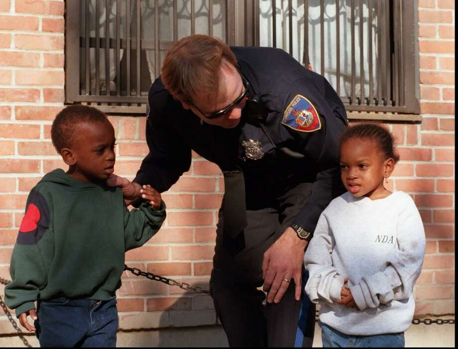 Officer Joe Kennedy meets twins, Kevin and Kemberly Jeanrene, 3, at the new police office in the Merrell Avenue housing complex on Oct. 30, 1997. Photo: Tom Ryan / File Photo