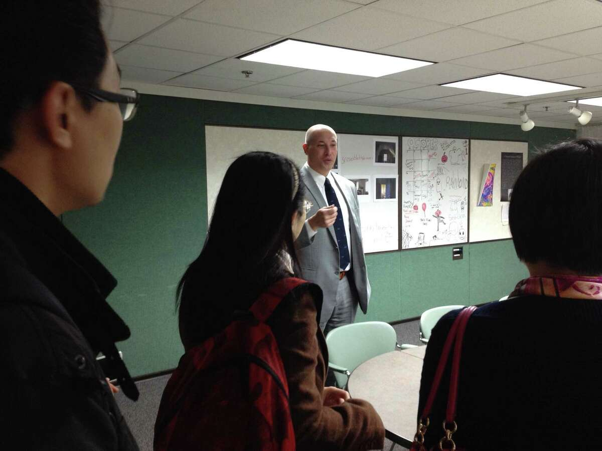 ACES ECA Principal Jason Hiruo guides members of an arts education delegation from Shanghai through the school's creative writing department.