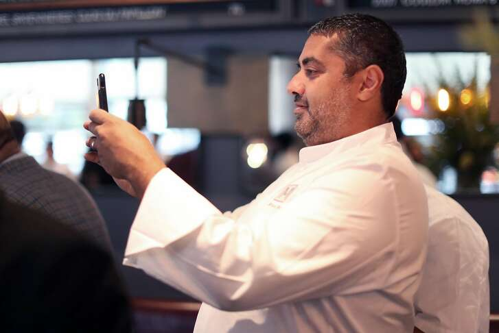 RN74 founder, Michael Mina, photographs original chef Jason Berthold as he leads the preshift meeting at RN74 in San Francisco, Calif., on Monday, September 18, 2017. The famed restaurant will serve its final meal on October 7th to make way for Ayesha Curry's new restaurant, International Smoke.