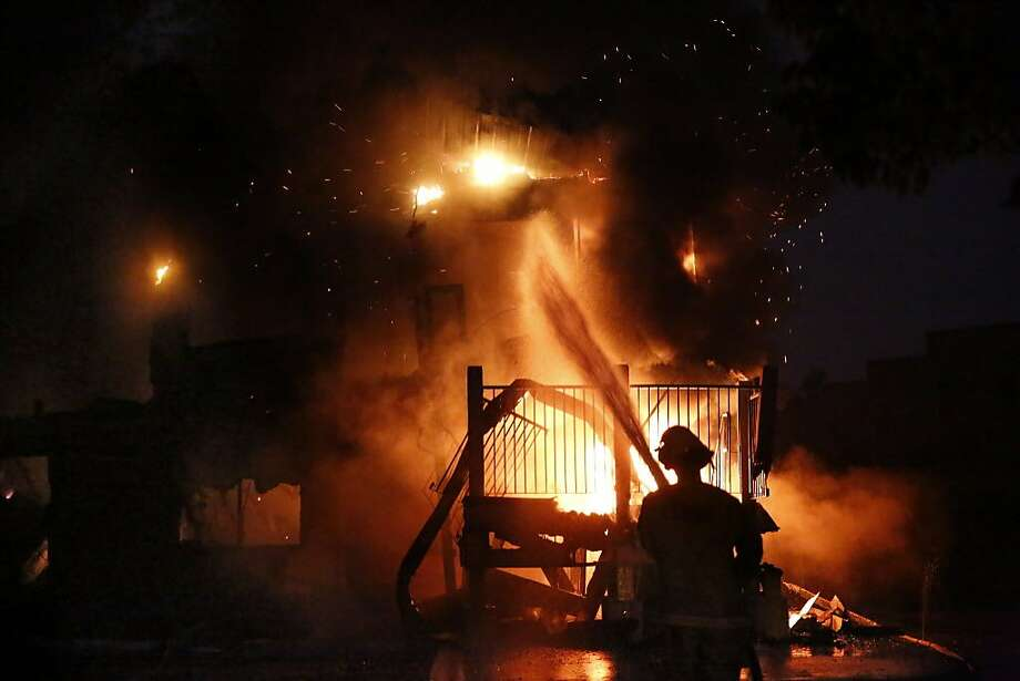 A firefighter pours water onto the America's Best Value Inn in Santa Rosa, which is a total loss in the fire. Photo: Michael Macor, The Chronicle