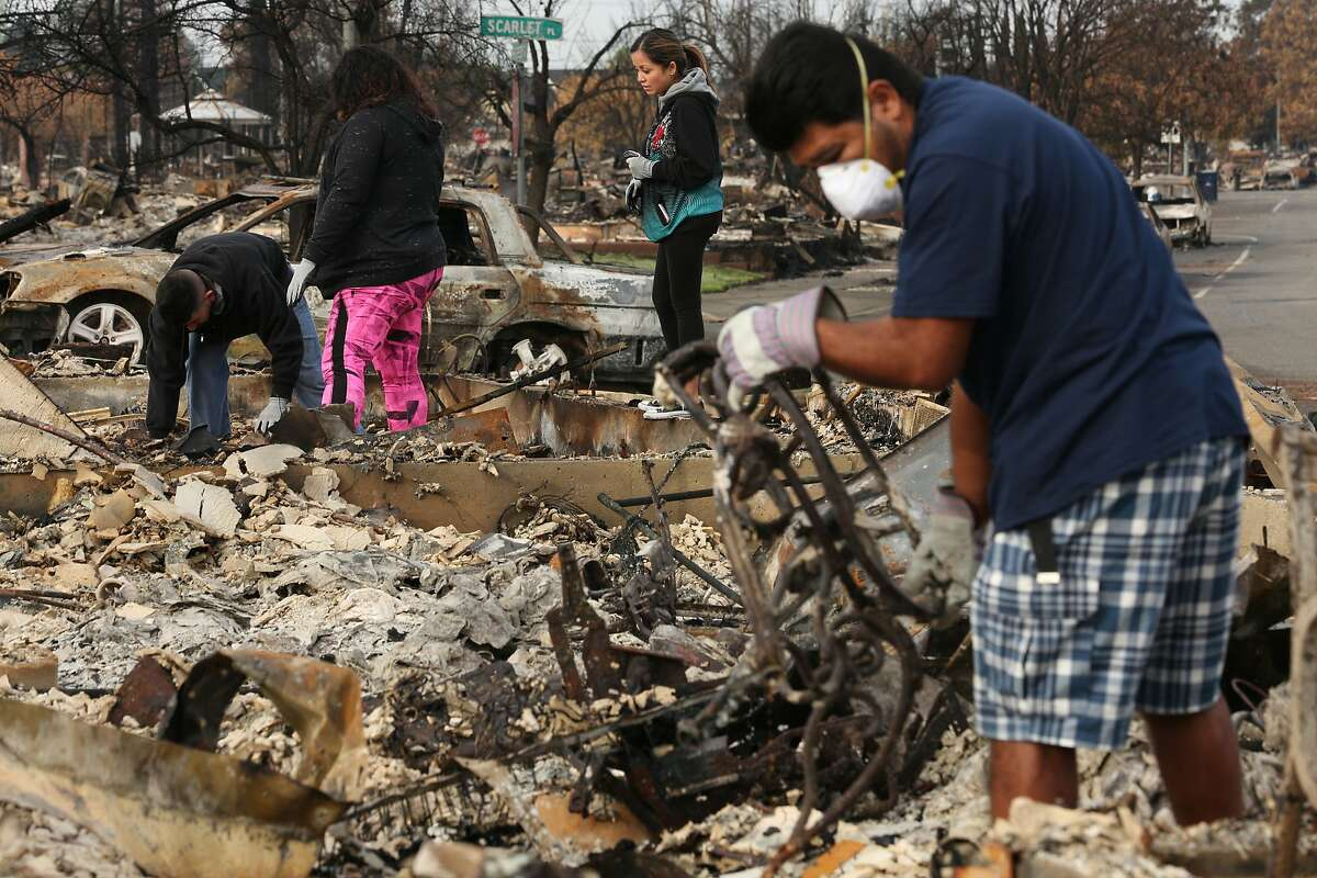 The Hernandez family search through the rubble to find their belongings in the Coffey Park neighborhood on Friday, Oct. 20, 2017, in Santa Rosa, Calif. Residents of the neighborhood were let back in for the first time since the Sonoma County fires to sift through what�s left.