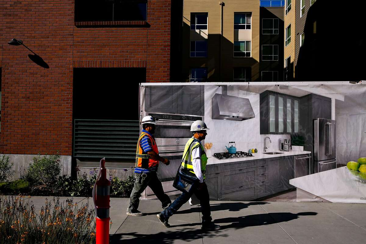People walk past the Avalon apartments in the Dogpatch neighborhood of San Francisco, Calif., on Thursday, Oct. 26, 2017.