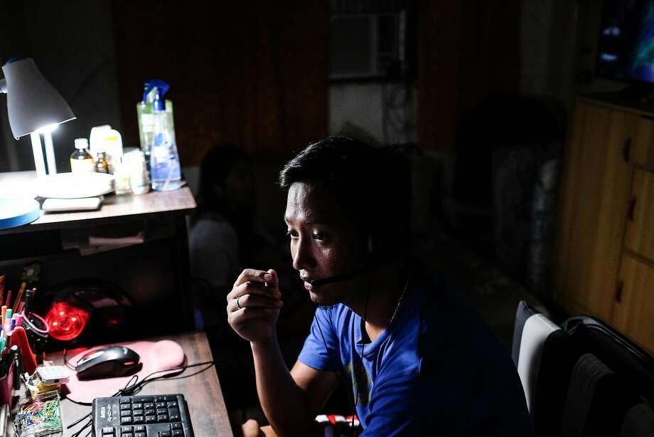 Rolando Cuartero checks on messages from his home office on a Saturday evening. Being able to work from home allows him to spend more time with his family. Photo: Veejay Villafranca, Veejay Villafranca For The San Francisco Chronicle