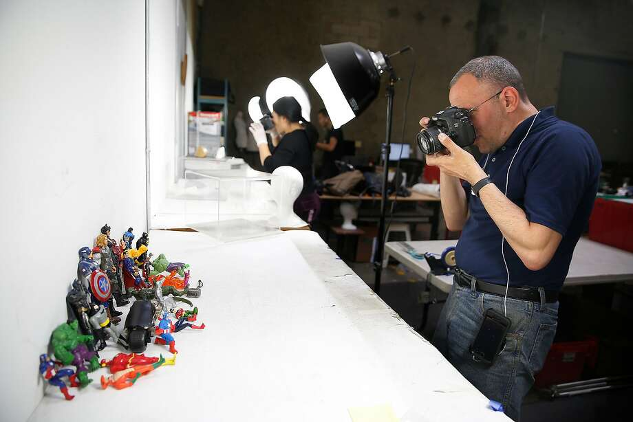 David Sament photographs action figures for Goodwill's website at the nonprofit's South San Francisco warehouse. Photo: Liz Hafalia, The Chronicle