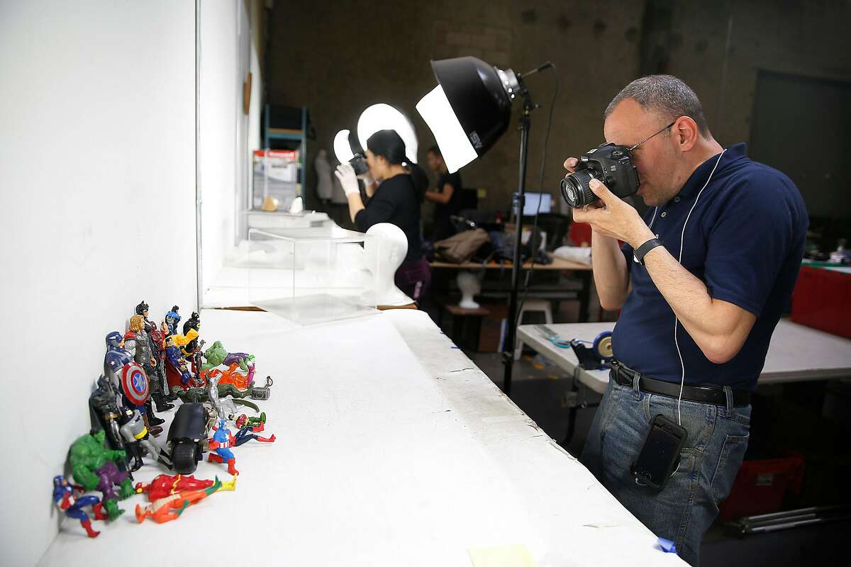 Photographer David Sament works with to action figures for the website at the Goodwill warehouse on Tuesday, October 17, 2017, in South San Francisco, Calif.