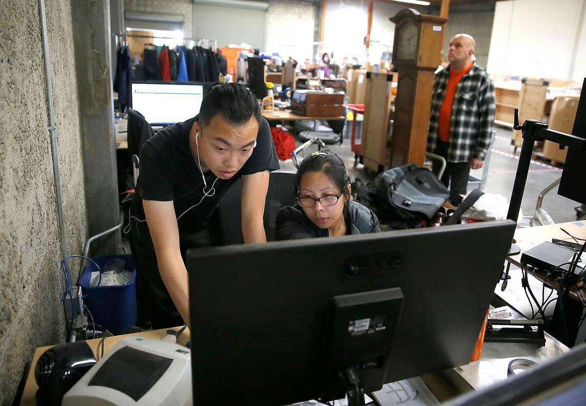 Photographer and evaluator Kenneth Kwan looks at listings for sfgoodwill.com at the Goodwill warehouse on Tuesday, October 17, 2017, in South San Francisco, Calif.