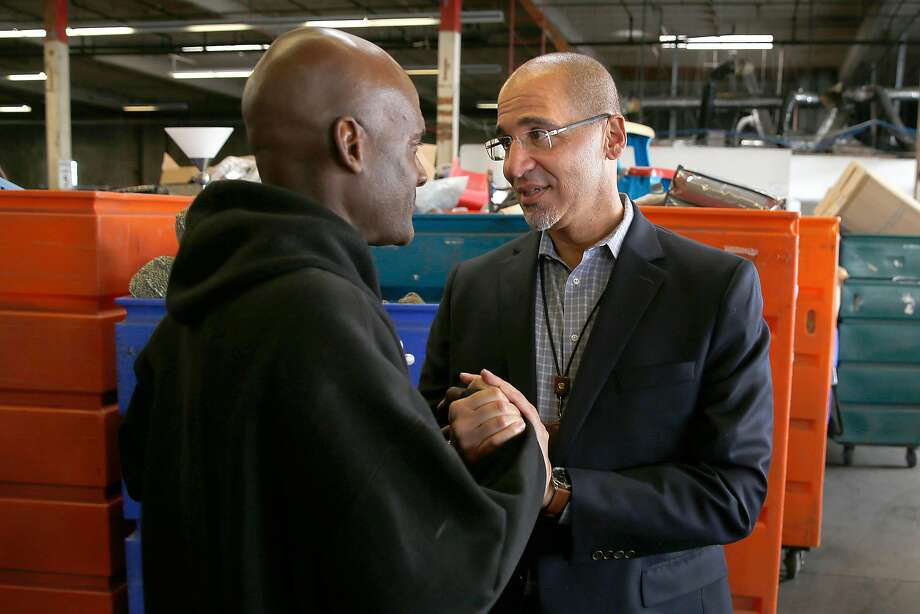Goodwill CEO and President William Rogers (right) talks with lead wares department worker Damon King at the South San Francisco warehouse. Photo: Liz Hafalia, The Chronicle