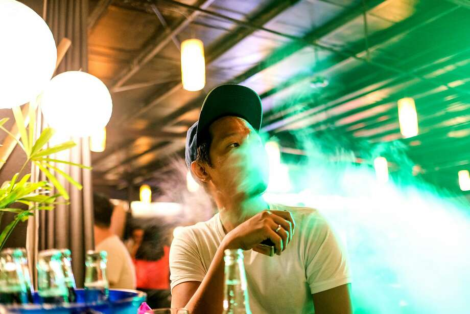 Cuartero enjoys a Saturday evening out with friends and fellow workers, below, in a bar in Quezon City. Photo: Veejay Villafranca, Veejay Villafranca For The San Francisco Chronicle