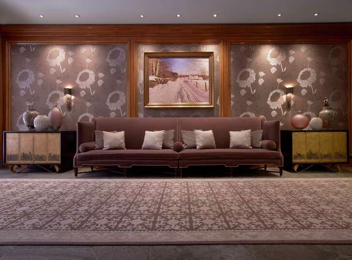 A hallway at the St. Regis Aspen Resort holds a 19th-century-style sofa, with wallpaper of oversize flowers and credenzas holding ceramic and metal vases, in the Beaux Arts style.