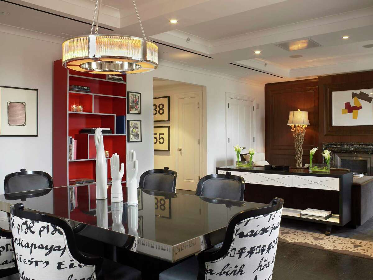 The dining area of the penthouse in New York's Surrey hotel was designed in the image of an Upper East Side home, with a chandelier and coffered ceiling. A Deco-style credenza separates it from the living area.