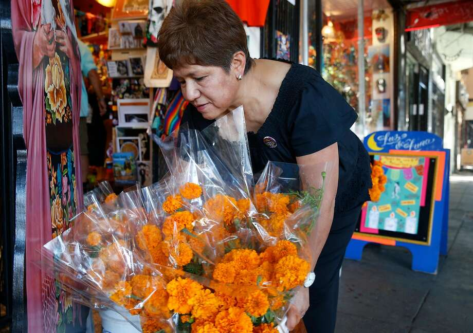 Top: Denise Gonzales arranges marigolds to sell at her Luz de Luna gift shop on 24th Street in preparation for Dia de los Muertos. Above: Shop shelves are lined with figurines for the day. Photo: Paul Chinn, The Chronicle