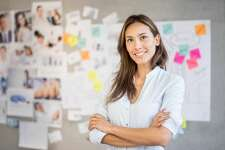 Successful Asian woman working at a creative office with a wall chart at the background