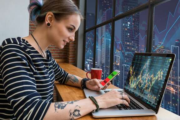Hipster young Woman freelancer using the technology laptop and smart phone mobile showing trading graph with the stock exchange trading graph screen background, Business financial and forex concept