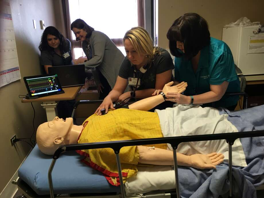 "Covenant Health Plainview Emergency Services manager Melissa Rodriguez and Providence St. Joseph Clinical Academy Manager Rachelle Ried watch Med-Surg Manager Rachel Prutzman and Women's Services Manager Danette Howell check the vital signs on the hospital's new training simulator, ""SimMan."""