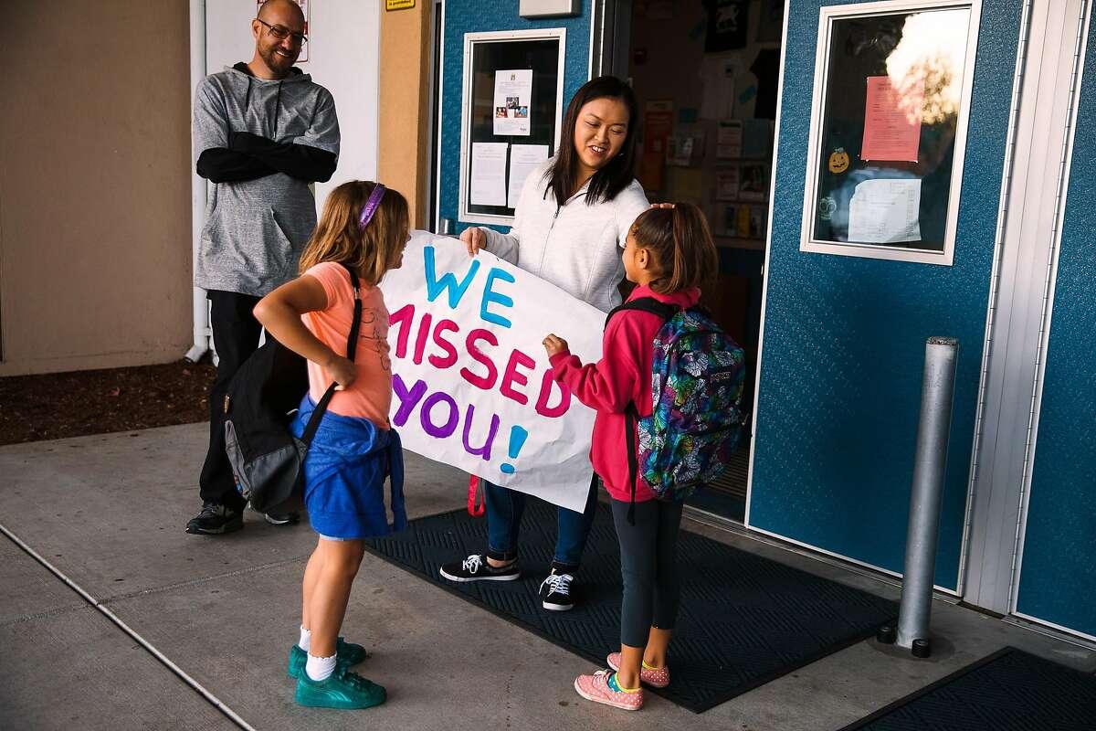 Second grade teacher, Liz Angle, greets students, Isabella Dunlap, 8, left, and Angeliz Ventura, 7, right, at James Monroe Elementary in Santa Rosa, Calif. Friday, October 27, 2017.