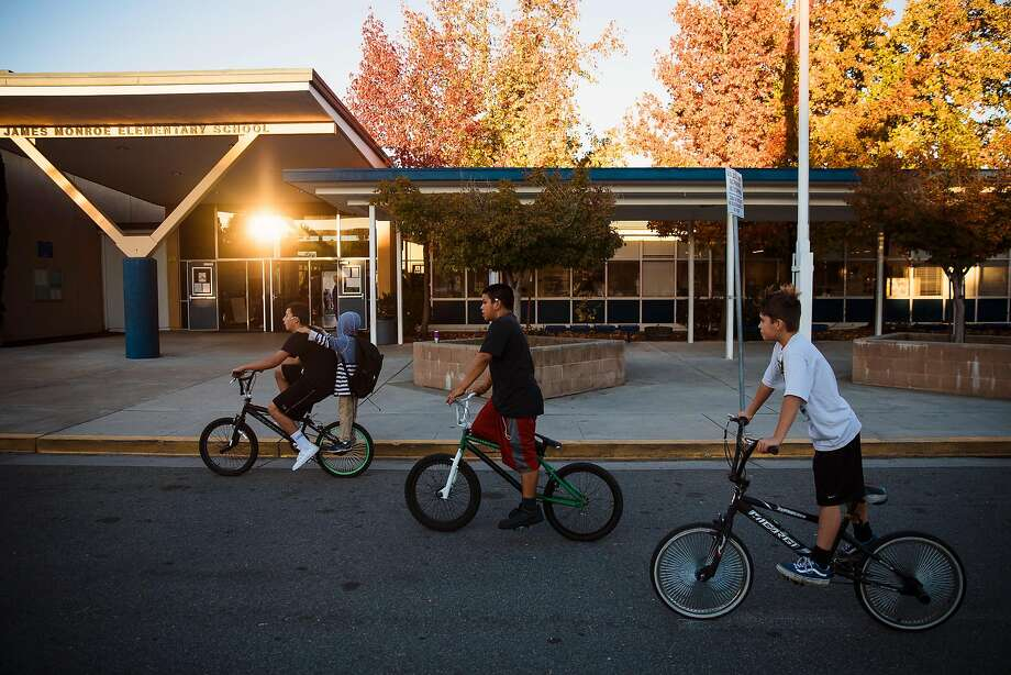 Students on bicycles return to James Monroe Elementary School in Santa Rosa, one of the 13 district schools that reopened. Photo: Mason Trinca, Special To The Chronicle