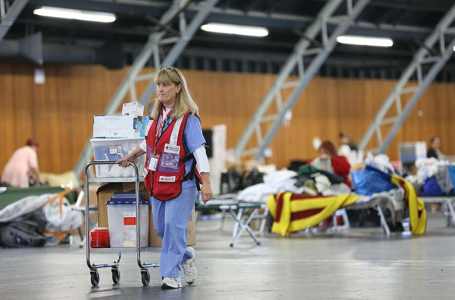 LPN Deborah Gensic moves medical supplies at Sonoma County Fairgrounds Red Cross shelter to the cafeteria. Photo: Liz Hafalia, The Chronicle