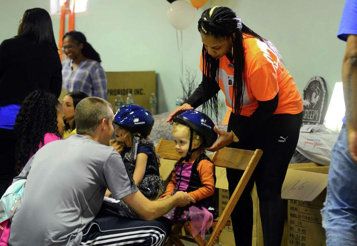 Lucy O'Connor, 2, of Stratford, gets fitted for a free bike helmet by Lincoln Tech nursing student Catanya during the 16th Annual Health and Safety Fair at Warsaw Park in Ansonia, Conn. on Friday Oct. 27, 2017. Griffin Hospital Community Outreach and Valley Parish Nurse Program, Safe Kids Greater Naugatuck Valley, Griffin Faculty Physicians, and Avangrid encouraged families to put on their Halloween costumes and come to a