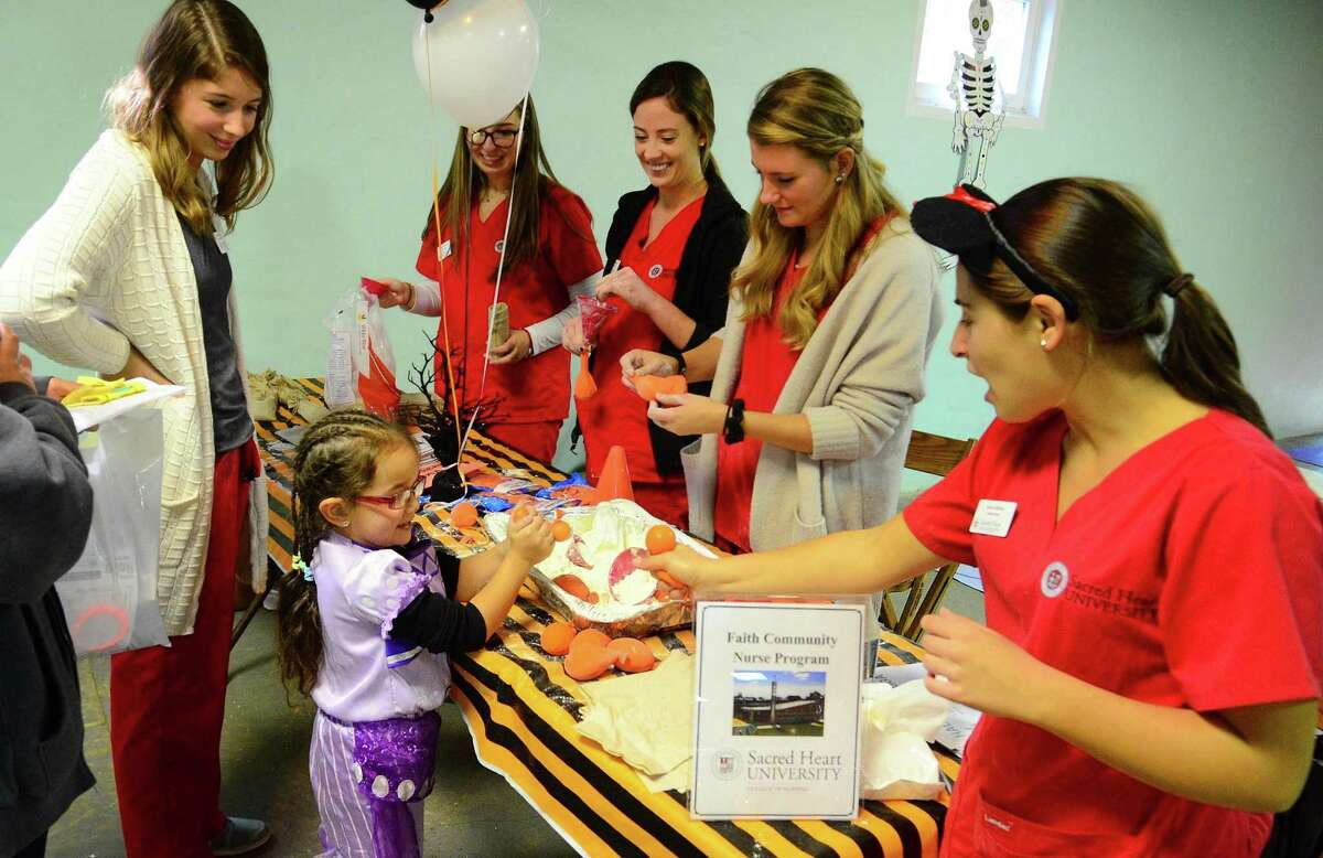 Sacred Heart University student nurse Jenna Hoffman, right, shows Hailey Vlasaty, 4, of Ansonia, how a stress ball works while helping her to make her own during the 16th Annual Children's Health and Safety Fair at Warsaw Park in Ansonia, Conn. on Friday Oct. 27, 2017. Griffin Hospital Community Outreach and Valley Parish Nurse Program, Safe Kids Greater Naugatuck Valley, Griffin Faculty Physicians, and Avangrid encouraged families to put on their Halloween costumes and come to a