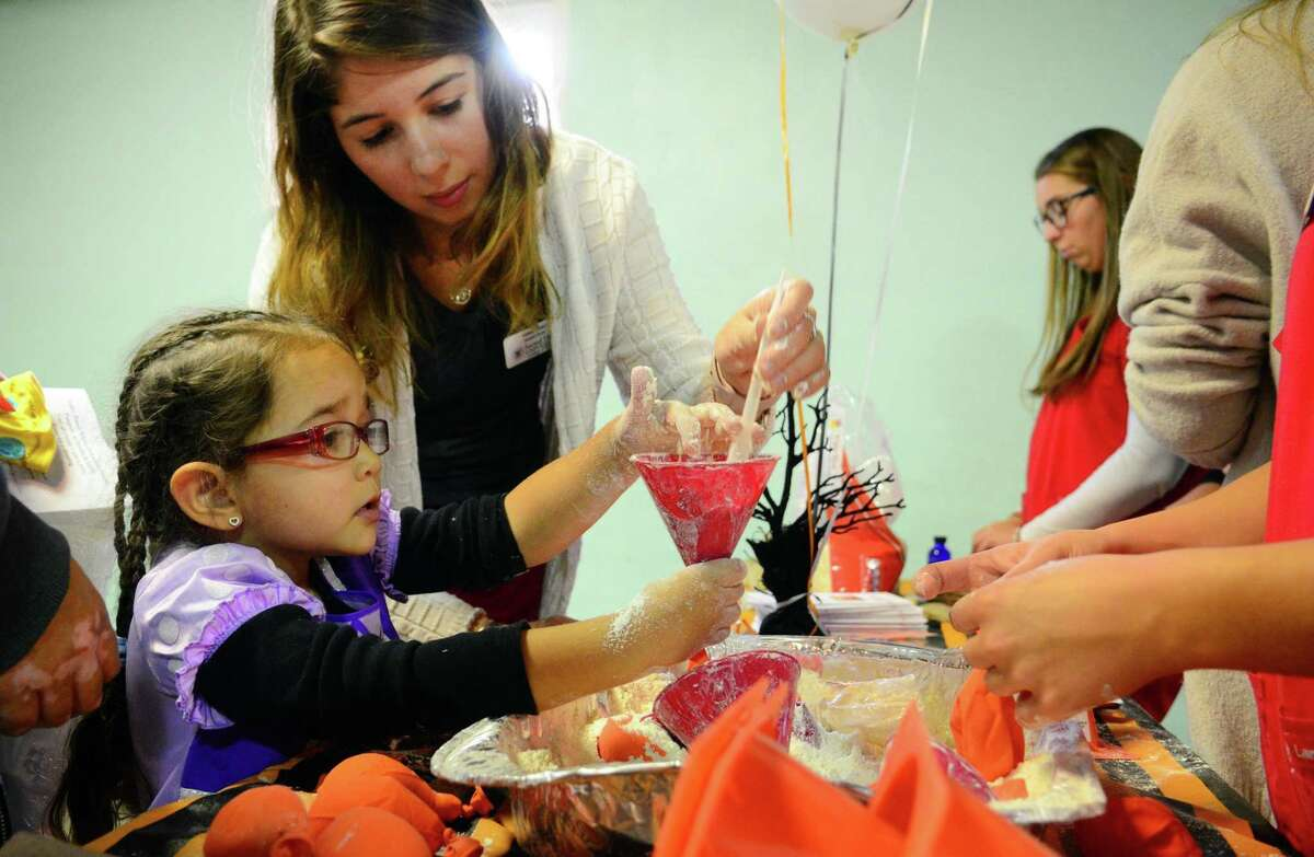 Sacred Heart University student nurse Helen Culici, shows Hailey Vlasaty, 4, of Ansonia, how make her own stress ball during the 16th Annual Children's Health and Safety Fair at Warsaw Park in Ansonia, Conn. on Friday Oct. 27, 2017. Griffin Hospital Community Outreach and Valley Parish Nurse Program, Safe Kids Greater Naugatuck Valley, Griffin Faculty Physicians, and Avangrid encouraged families to put on their Halloween costumes and come to a