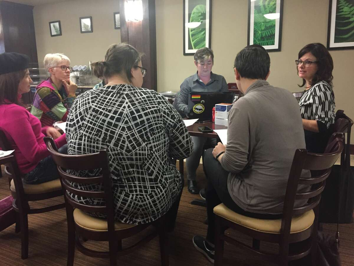 Maureena Benavides, far right, and Kerry Manzo, with laptop, finalize plans and details with volunteers for the symposium at Sleep Inn and Suites where the two-day event will be held
